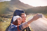 Young couple with backpacks hiking taking selfie with camera phone on sunny, remote road - CAIF05082