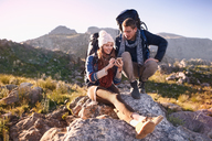 Young couple with backpacks hiking, resting on rock using smart phone - CAIF05085