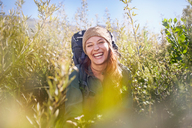 Portrait laughing young woman with backpack hiking in sunny field - CAIF05088