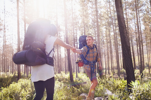 Young man helping girlfriend on hiking trail in sunny woods - CAIF05094