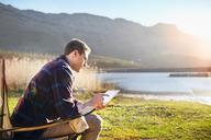 Young man using digital tablet at sunny lakeside - CAIF05100