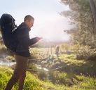 Young man with backpack hiking, checking smart phone in sunny field - CAIF05103