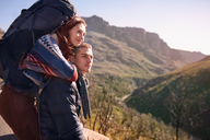 Affectionate young couple with backpack hiking, taking a break in sunny landscape - CAIF05106