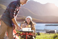 Young couple camping, cooking at camping stove at sunny lakeside - CAIF05109