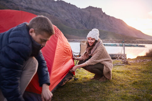 Young couple pitching tent at lakeside campsite - CAIF05112