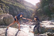 Young man helping girlfriend hiking, crossing sunny rocks in stream - CAIF05127