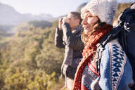 Young couple hiking, looking at sunny view with binoculars - CAIF05130