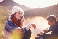 Smiling young woman talking on cell phone at sunny, remote roadside - CAIF05142