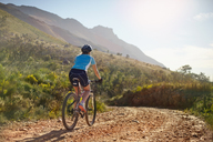 Young woman mountain biking on sunny, remote dirt road - CAIF05163