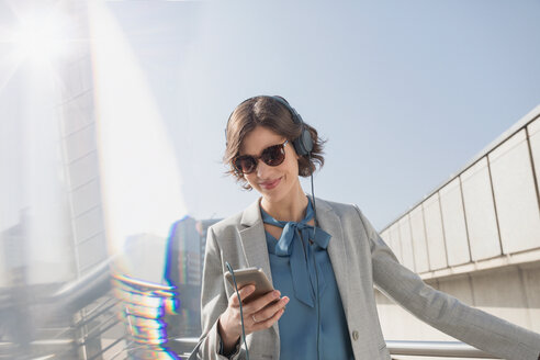 Smiling businesswoman with sunglasses listening to music with smart phone and headphones - CAIF05196