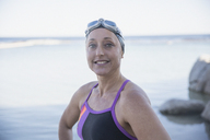 Portrait smiling confident female open water swimmer at ocean - CAIF05229