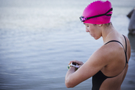 Female open water swimmer checking smart watch at ocean - CAIF05244