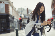 Young woman commuting on bicycle, texting with cell phone on sunny urban street - CAIF05259