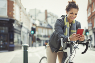 Smiling young woman commuting with bicycle, texting with cell phone on sunny urban street - CAIF05265