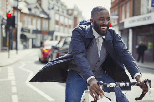Smiling young businessman commuting, riding bicycle on sunny urban street - CAIF05271