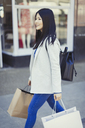 Young woman walking along storefront with shopping bags - CAIF05280