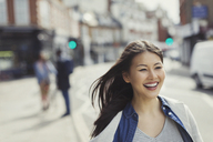 Smiling, enthusiastic young woman walking on sunny urban street - CAIF05283