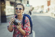 Portrait laughing, enthusiastic young female tourist in sunglasses photographing with camera on urban street - CAIF05289