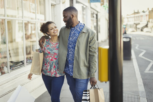 Affectionate young couple with shopping bags walking along urban storefront - CAIF05295