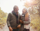 Affectionate senior couple walking arm in arm on path in autumn park - CAIF05313
