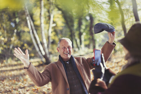 Senior man posing for wife with camera phone in autumn park - CAIF05316