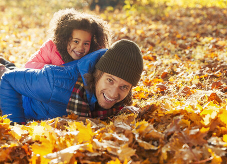 Portrait playful daughter laying on father in autumn leaves in sunny park - CAIF05322