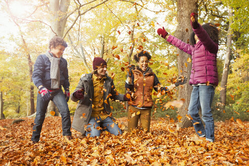 Playful young family throwing leaves in autumn woods - CAIF05325