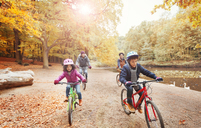 Young family bike riding along pond in autumn park - CAIF05328