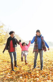 Parents swinging daughter in sunny autumn park - CAIF05337