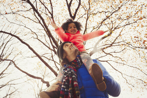 Father carrying daughter on shoulders under tree in autumn park - CAIF05340