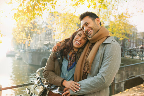 Laughing young couple hugging on autumn bridge over canal in Amsterdam - CAIF05355