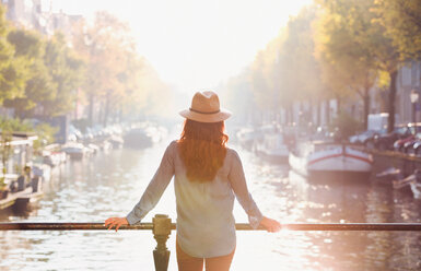 Woman wearing hat looking at sunny autumn canal view, Amsterdam - CAIF05358