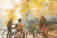 Friends with bicycles along sunny autumn canal in Amsterdam - CAIF05361