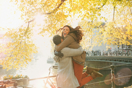 Enthusiastic couple hugging along sunny autumn canal, Amsterdam - CAIF05367