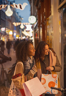 Young women window shopping at storefront on urban night street - CAIF05373