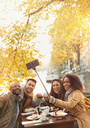 Smiling friends taking selfie with selfie stick at autumn sidewalk cafe - CAIF05376