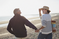 Laughing mature couple holding hands and walking on sunny beach - CAIF05388