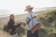 Husband helping wife on sunny beach grass path - CAIF05409