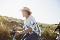 Playful mature woman riding bicycle on sunny beach grass path - CAIF05418