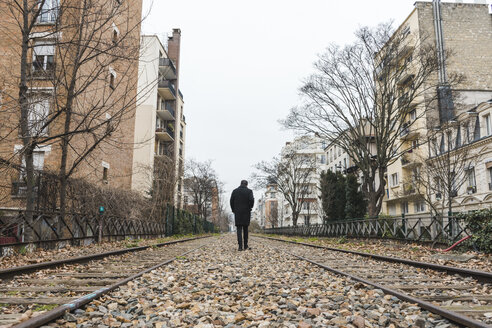 France, Paris, back view of man walking along abandoned railway tracks - AFVF00280