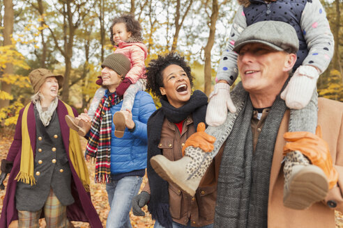 Playful multi-generation family walking in autumn park - CAIF05430
