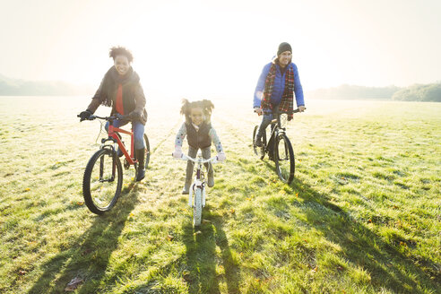 Portrait young family bike riding in sunny autumn park grass - CAIF05442