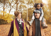 Laughing senior couple carrying daughter on shoulders in autumn woods - CAIF05445