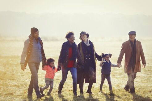 Multi-generation family holding hands walking in sunny autumn grass - CAIF05448