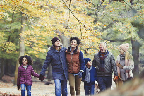 Multi-generation family walking in autumn woods - CAIF05451
