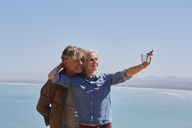 Affectionate senior couple taking selfie overlooking sunny ocean view - CAIF05454