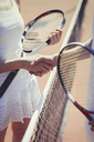 Tennis players handshaking in sportsmanship at net on sunny tennis court - CAIF05487