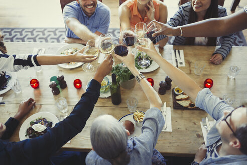 Overhead view friends toasting wine glasses at restaurant table - CAIF05550