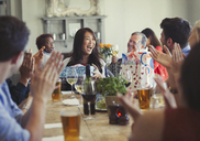 Friends clapping for happy woman celebrating birthday at restaurant table - CAIF05562
