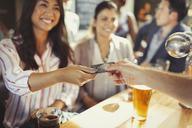 Smiling woman paying bartender with credit card at bar - CAIF05568